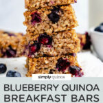 stack of blueberry quinoa breakfast bars on a cutting board with fresh blueberries