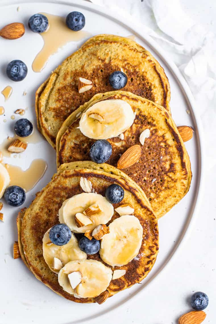 overhead of three banana protein pancakes on a white plate with fresh fruit and maple syrup toppings