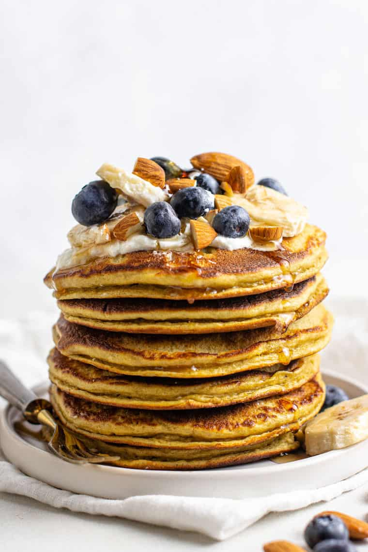 stack of banana protein pancakes with fresh blueberries, maple syrup, almonds and bananas on top
