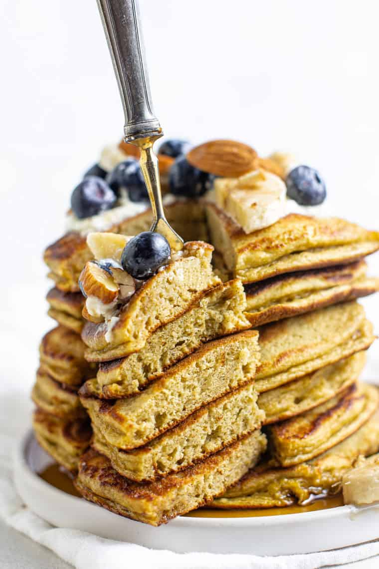 stack of gluten-free protein pancakes with a slice removed on a fork topped with banana, blueberries and almonds