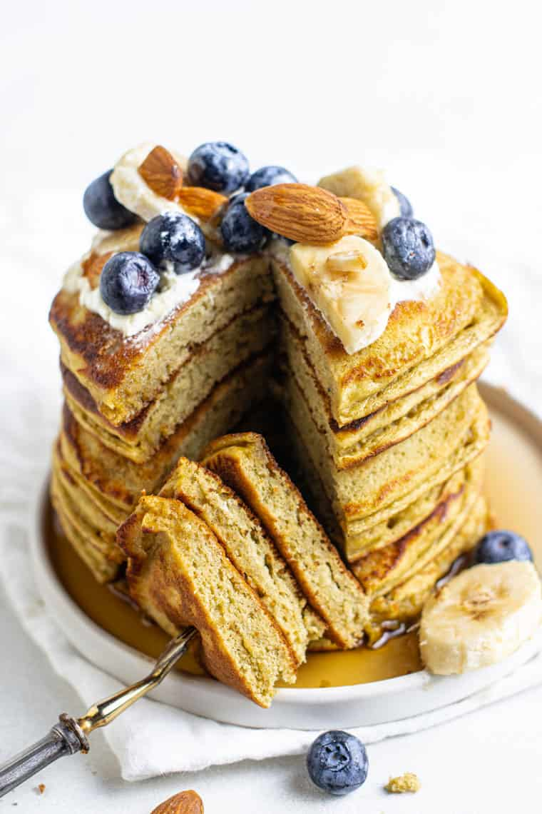 stack of gluten free protein pancakes with blueberries, almonds and banana slices on a white plate with a slice removed by a fork
