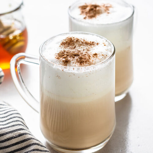 side view of two glass mugs of london fog lattes topped with cinnamon