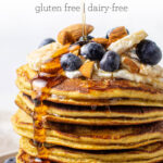 stack of protein pancakes with yogurt, berries, syrup, and almonds