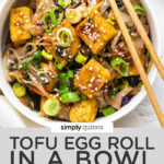 overhead of a white bowl with crispy tofu egg roll topped with sesame seeds