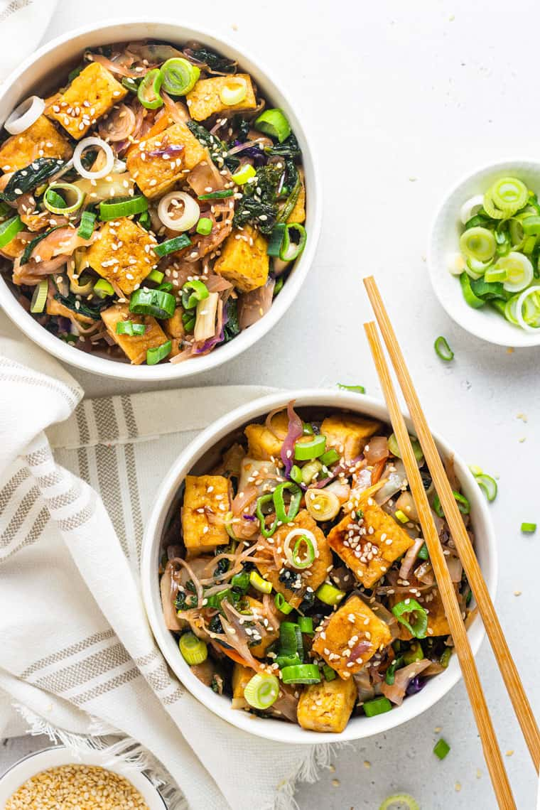 overhead of two white bowls with tofu egg roll stir fries with wooden chopsticks