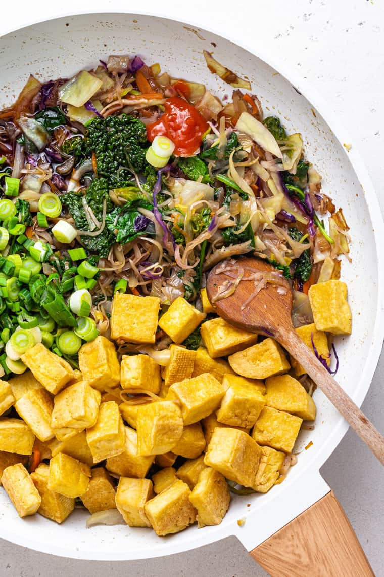 overhead of a white frying pan with ingredients for tofu egg roll bowls and a wooden spoon