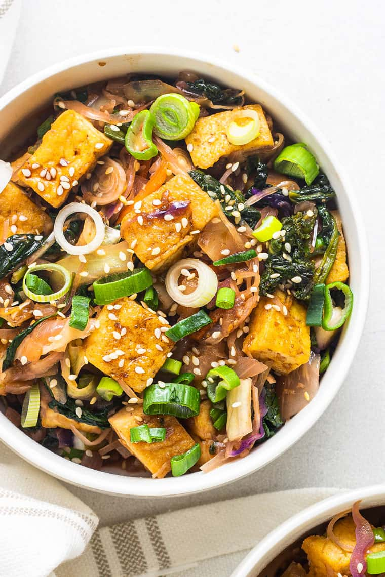 overhead of a white bowl with vegan tofu and greens