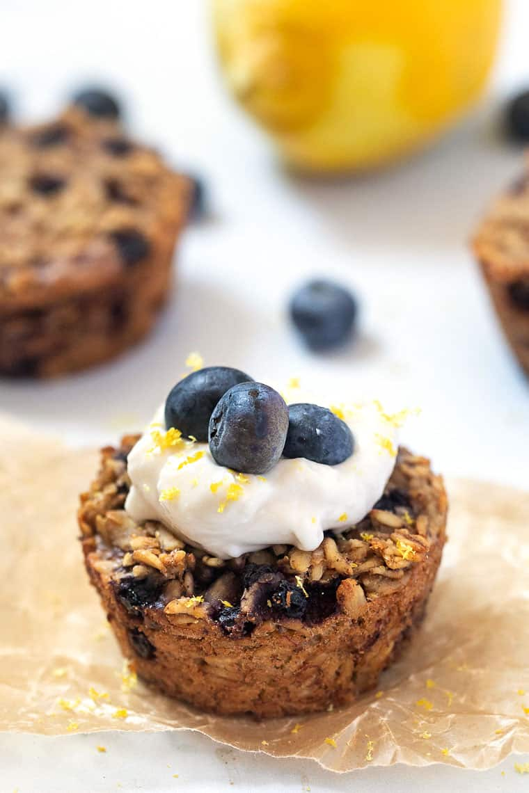 close up baked oatmeal cups with blueberries and lemon zest topped with yogurt and fresh blueberries
