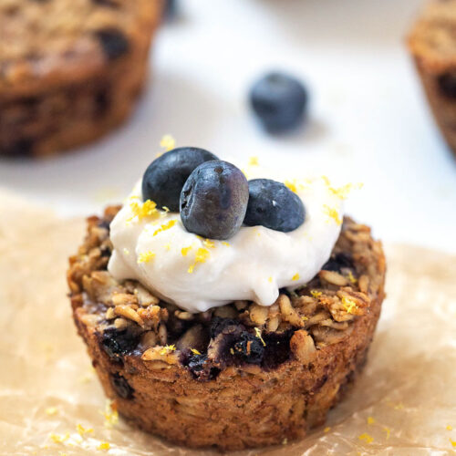 close up baked oatmeal cups with blueberries and lemon zest and topped with yogurt and blueberries