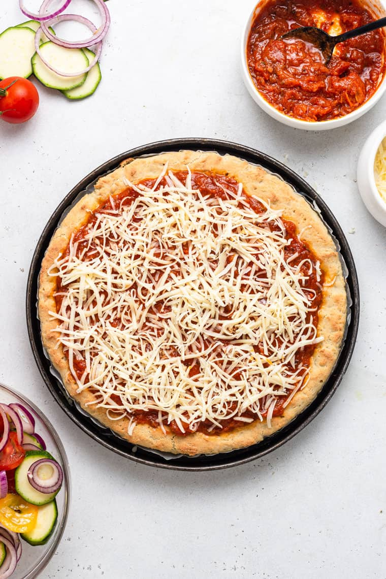 overhead of unbaked gluten-free pizza crust with sauce and cheese
