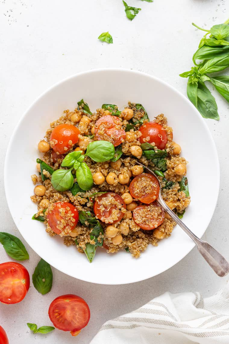 overhead of a white bowl with fresh tomato and basil quinoa salad