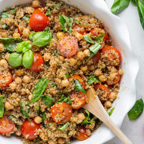 overhead of white bowl with quinoa caprese salad and fresh basil