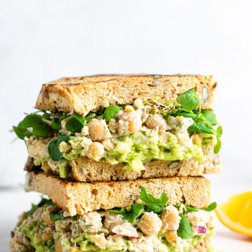 side view of two chickpea caesar salad sandwiches on toast