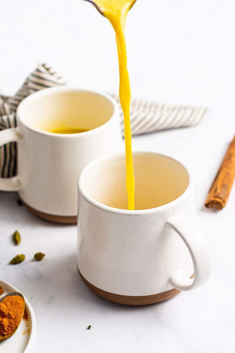 pouring turmeric latte into a white mug