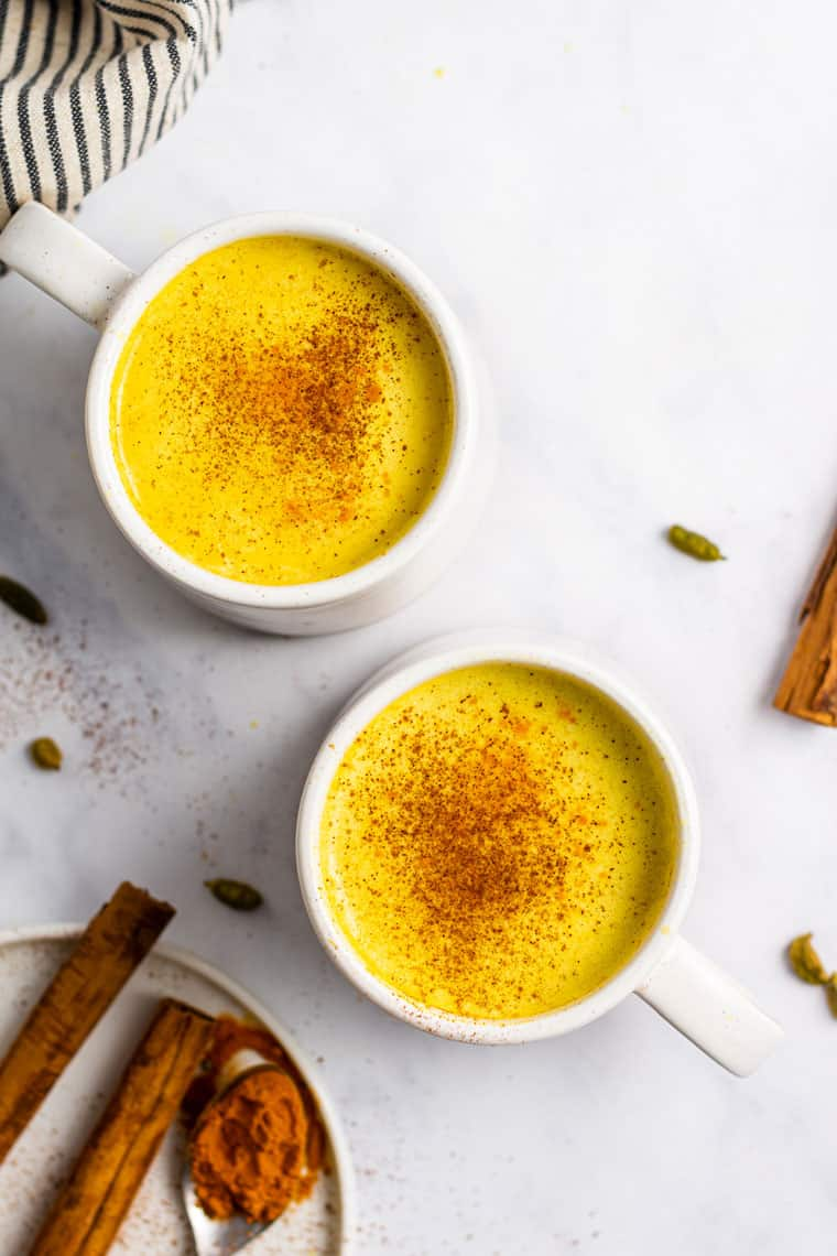 overhead of two white mugs with turmeric lattes