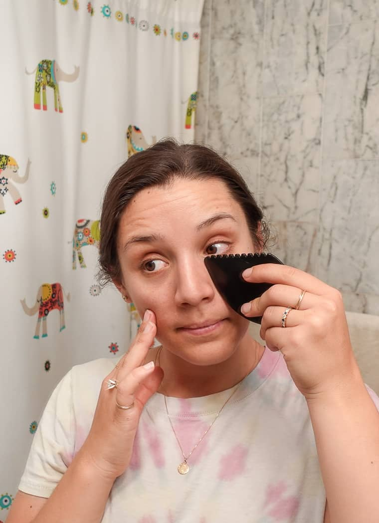 woman using black gua sha tool under eye