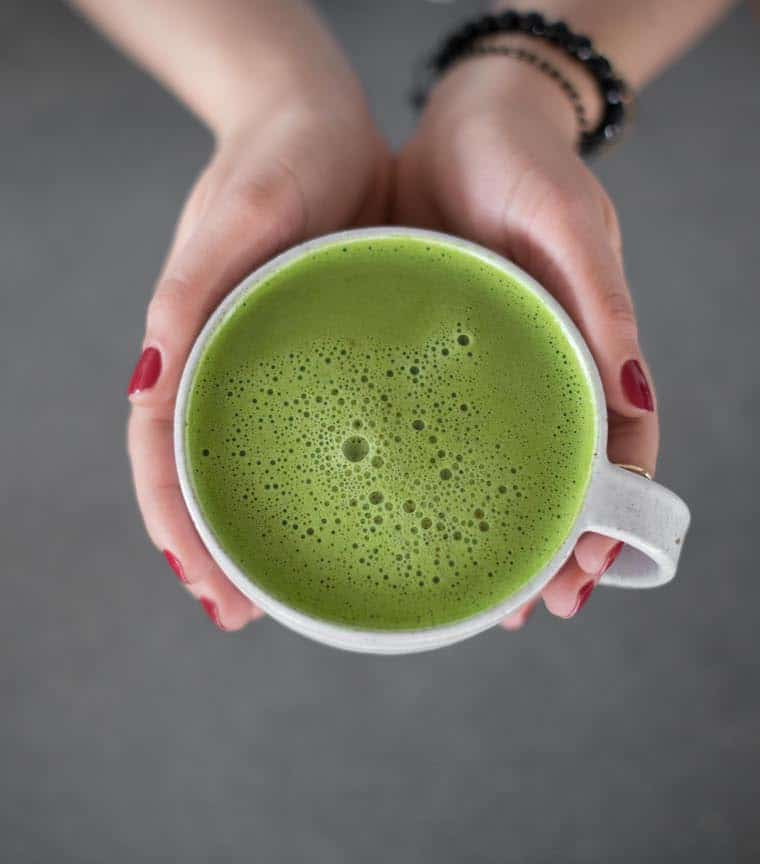 overhead of two hands holding a white mug with a matcha green tea latte inside