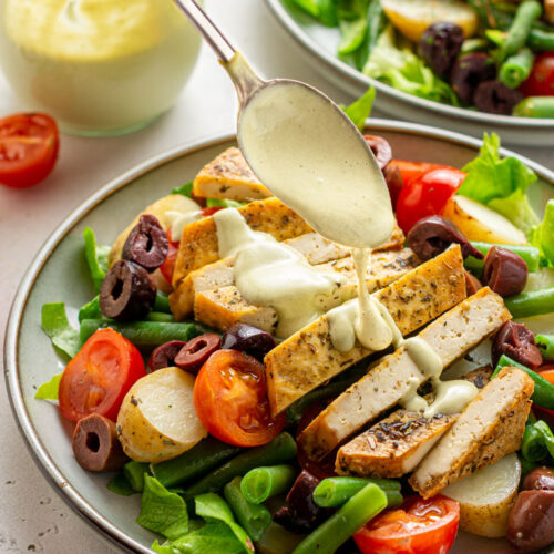 close up on a spoon drizzling dressing on top of sliced tofu with salad under