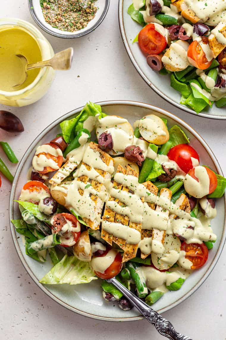 overhead of two plates with nicoise salad topped with sliced tofu and creamy dressing