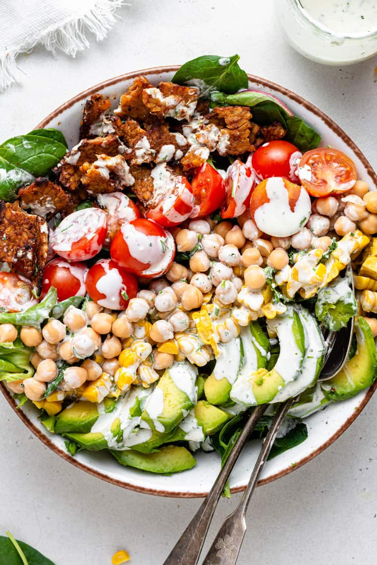 overhead of a bowl with layered vegan cobb salad and creamy dressing