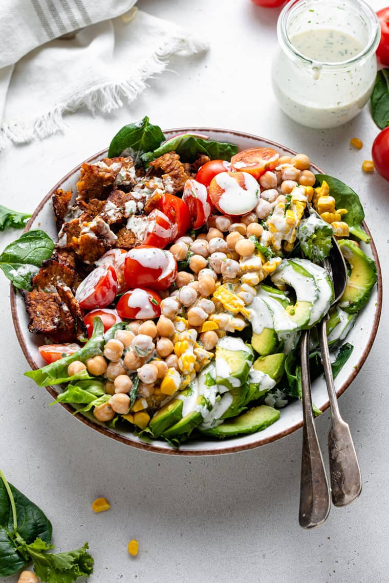 overhead of a large serving bowl with vegan cobb salad tomatoes, chickpeas and tempeh bacon with creamy dressing