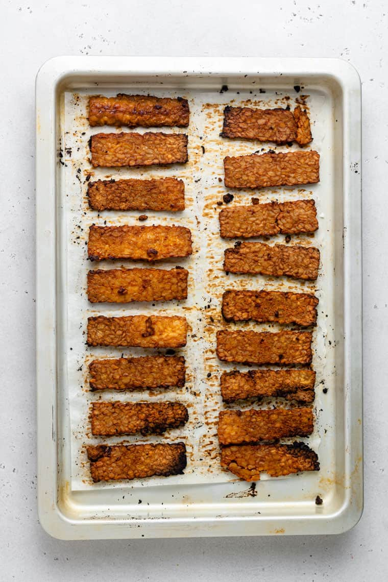 overhead of a baking sheet with two rows of tempeh bacon