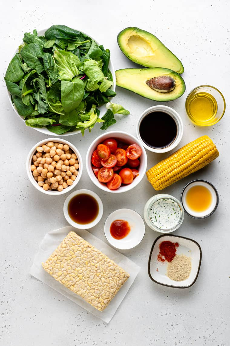 overhead of ingredients for vegan cobb salad with vegetables, corn, tempeh bacon and avocado