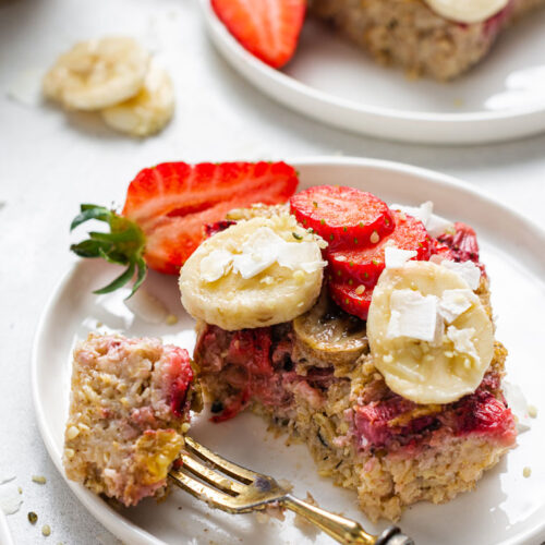 close up on a square of strawberry baked oats topped with fresh fruit