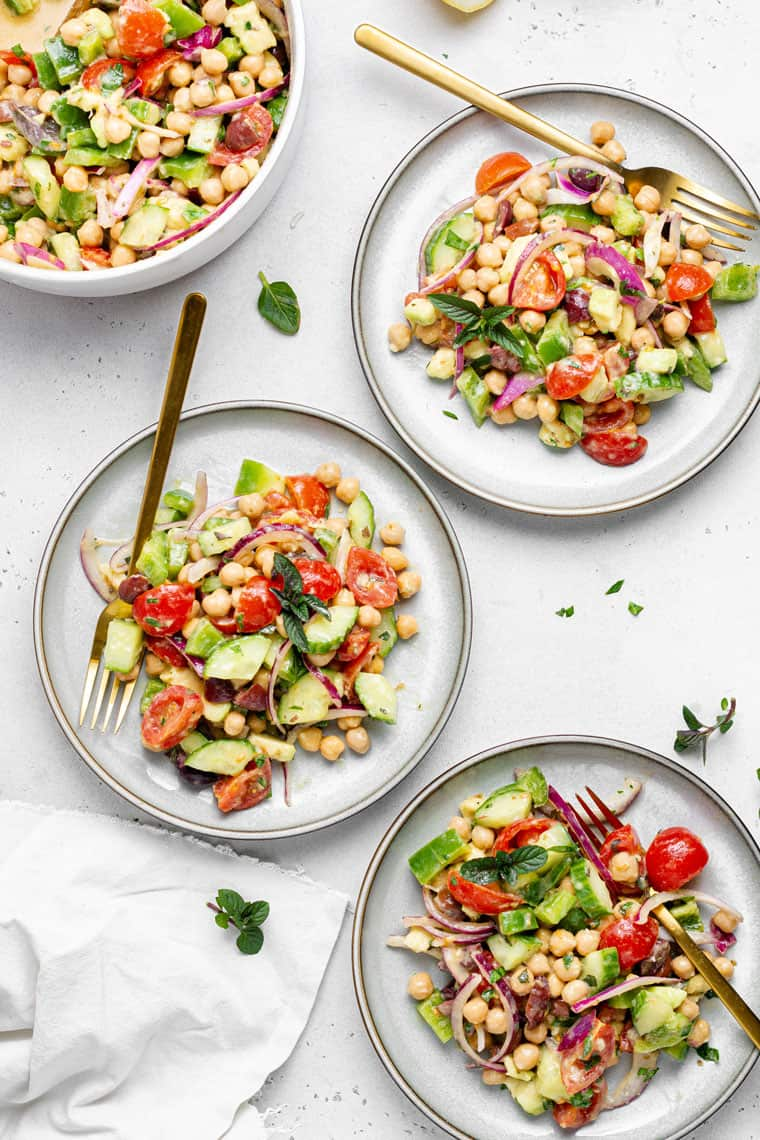 three plate filled with chickpea and vegetable salad