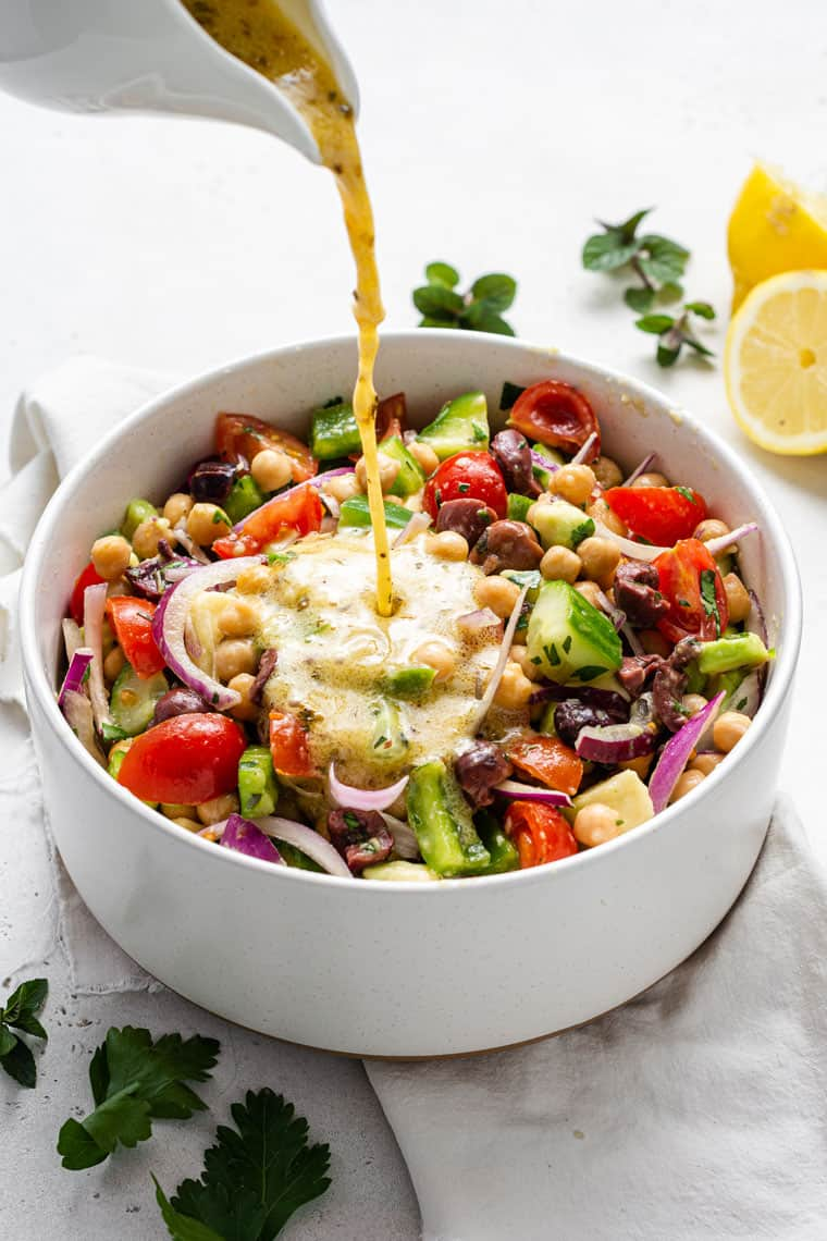 pouring dressing over chickpea and vegetable salad in a white bowl