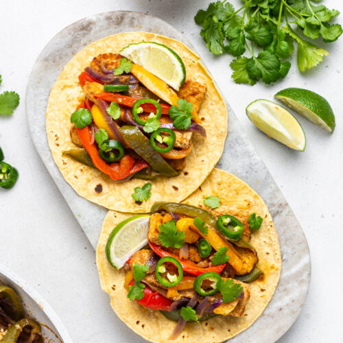 overhead of a marble platter with two vegan tempeh fajitas