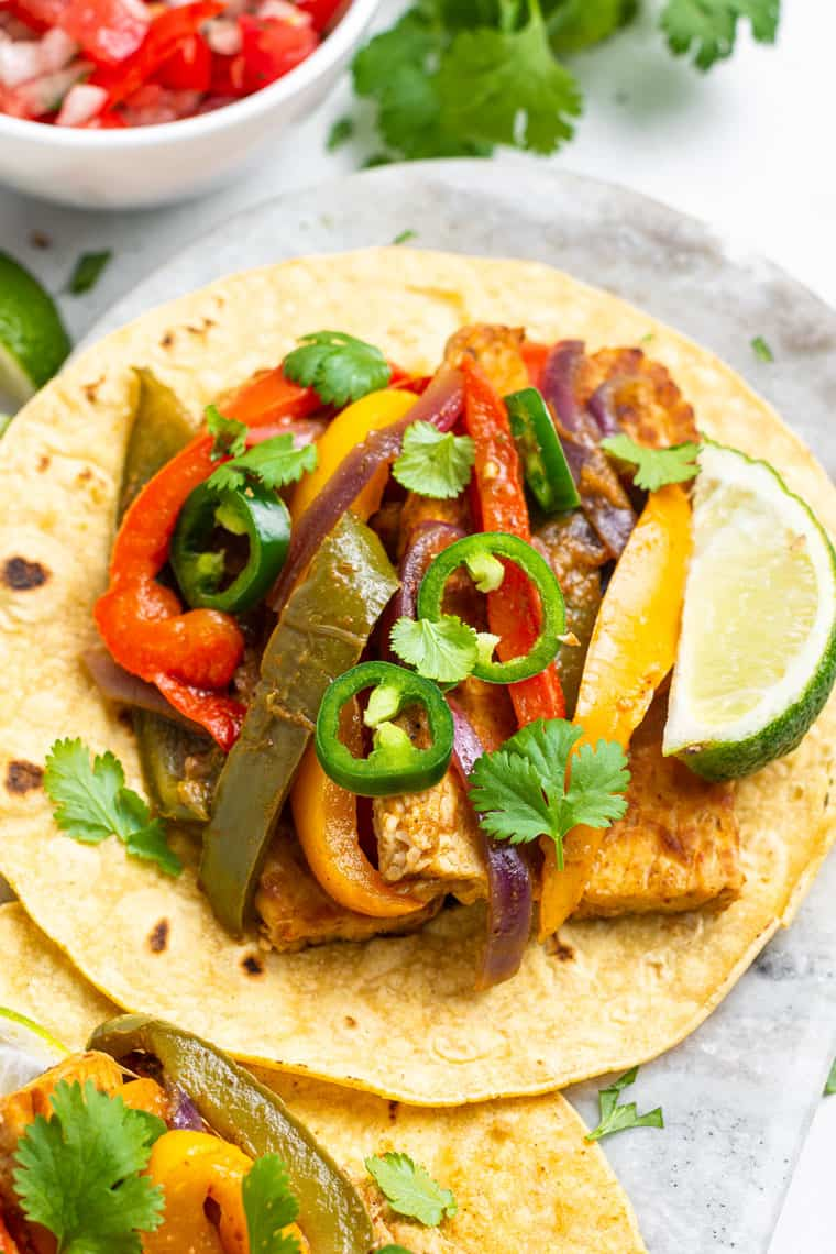 close up on a tempeh fajita with peppers, lime and jalapenos