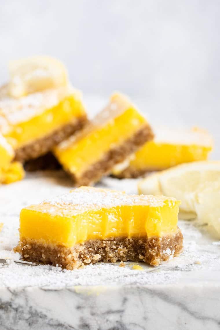 bitten-into dairy-free lemon bar with almond crust