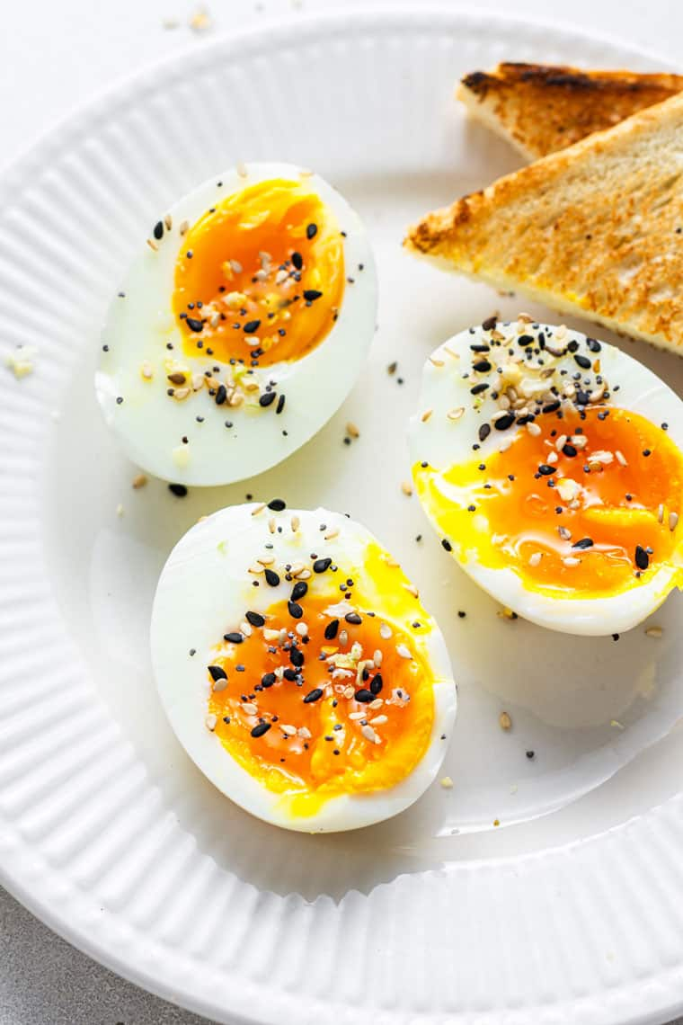 three soft boiled eggs on a plate with corners of toast