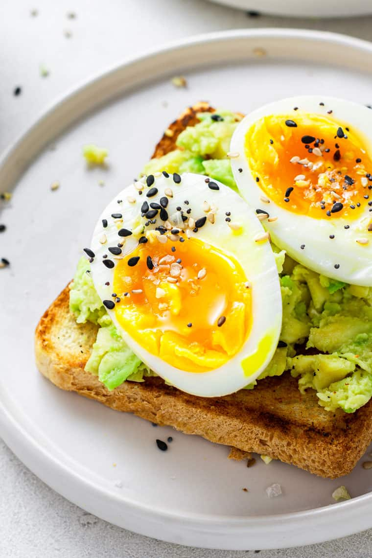 close up on avocado toast with soft boiled eggs and sesame seeds