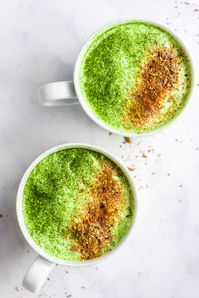 two white mugs of matcha latte with umpkin spice on top