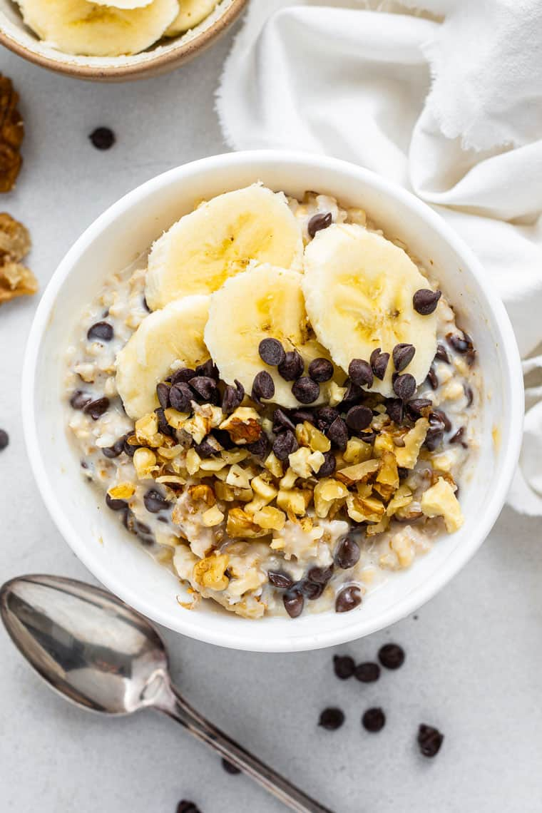 white bowl of overnight oats with chocolate chips and banana slices
