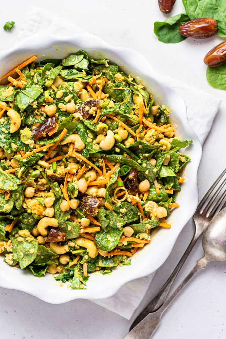 white bowl of moroccan chickpea and quinoa salad with carrots and dates