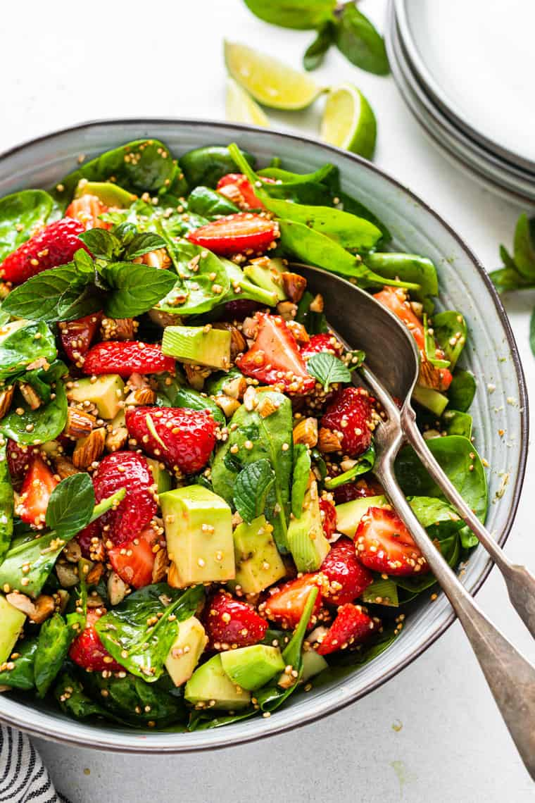 bowl of strawberry spinach avocado salad with dressing
