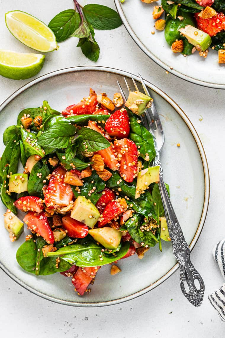 close up on a plate of strawberry spinach and quinoa salad
