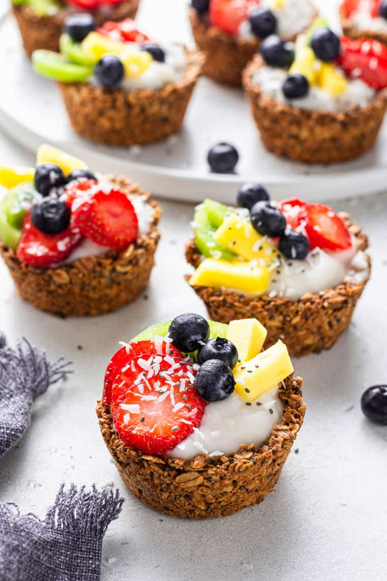 three oatmeal cups filled with yogurt and fruit