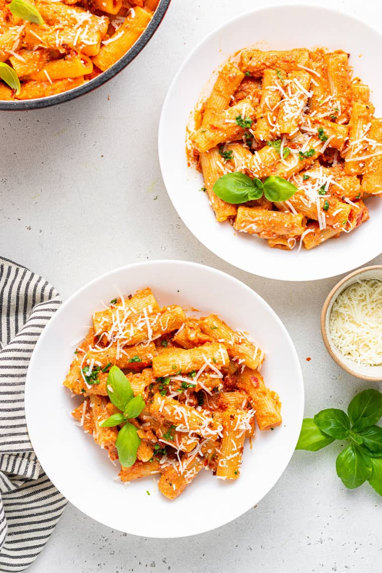 two plates of vegan vodka sauce pasta with fresh basil and grated cheese on top