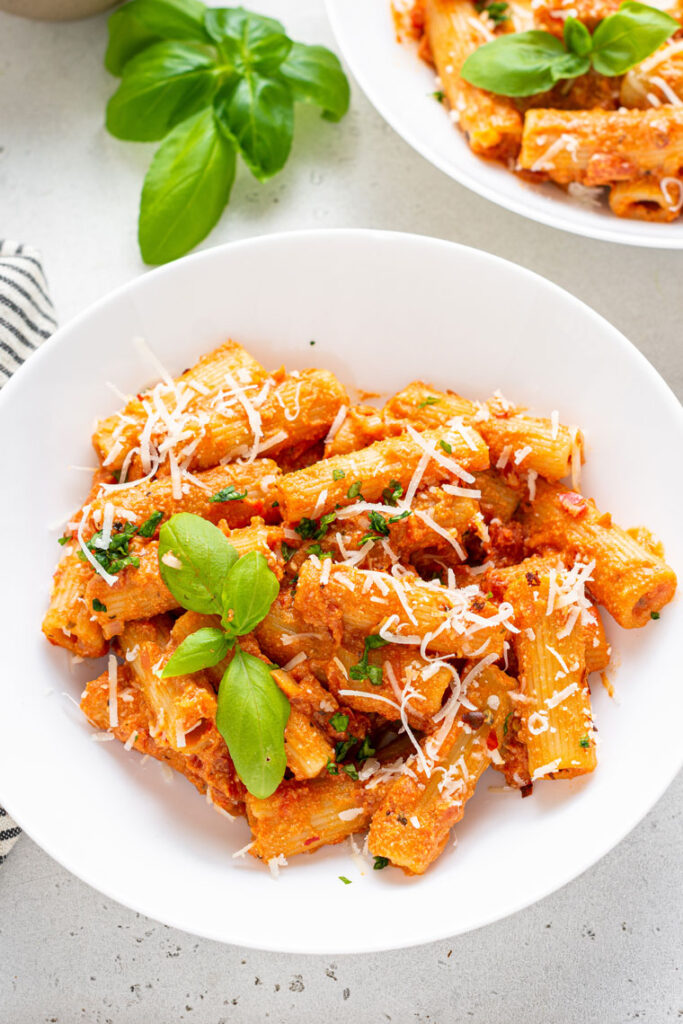 white plate with vegan vodka pasta sauce served over rigatoni noodles with basil and grated cheese