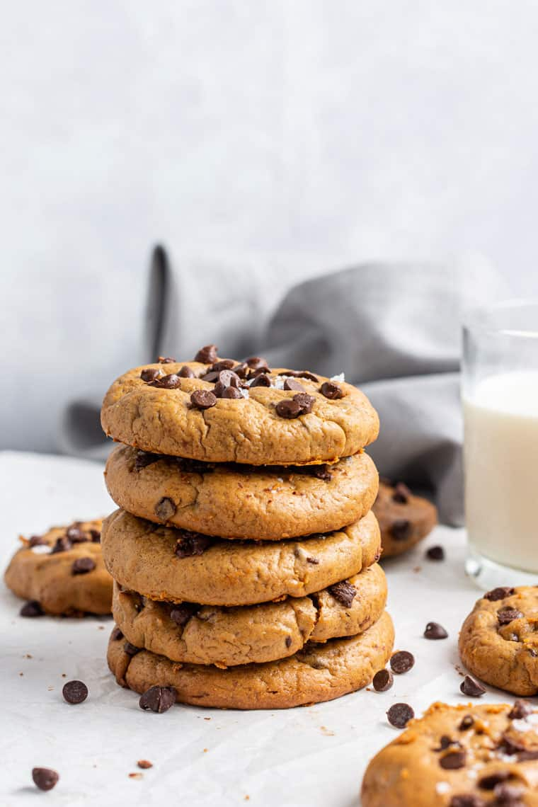 stack of several almond butter chocoalte chip cookies with a glass of milk