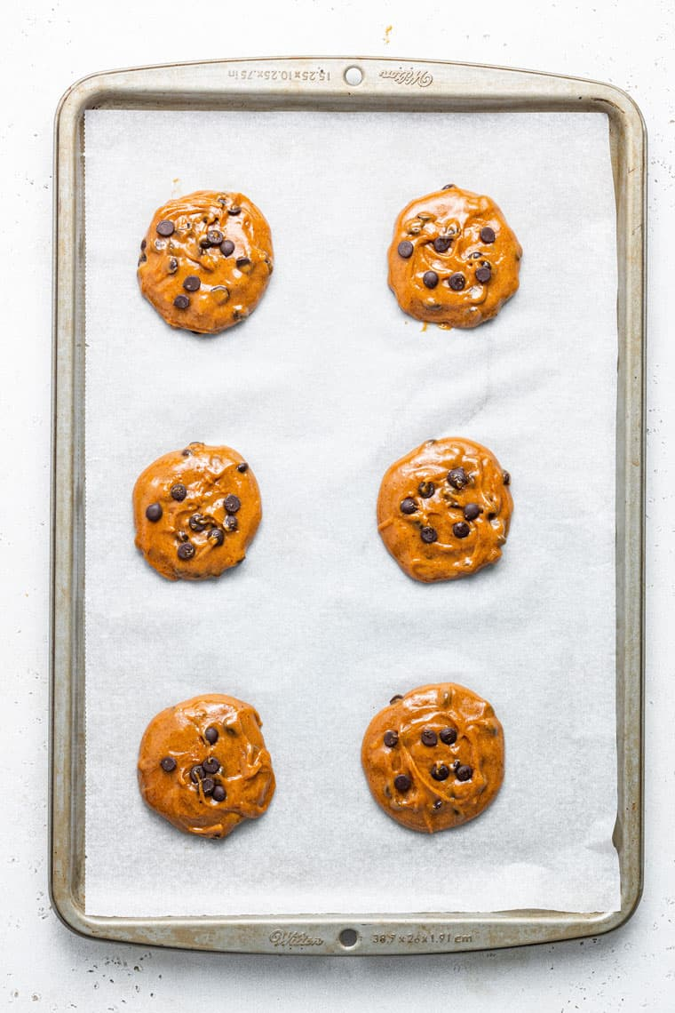 baking sheet with six raw chocolate chip cookies