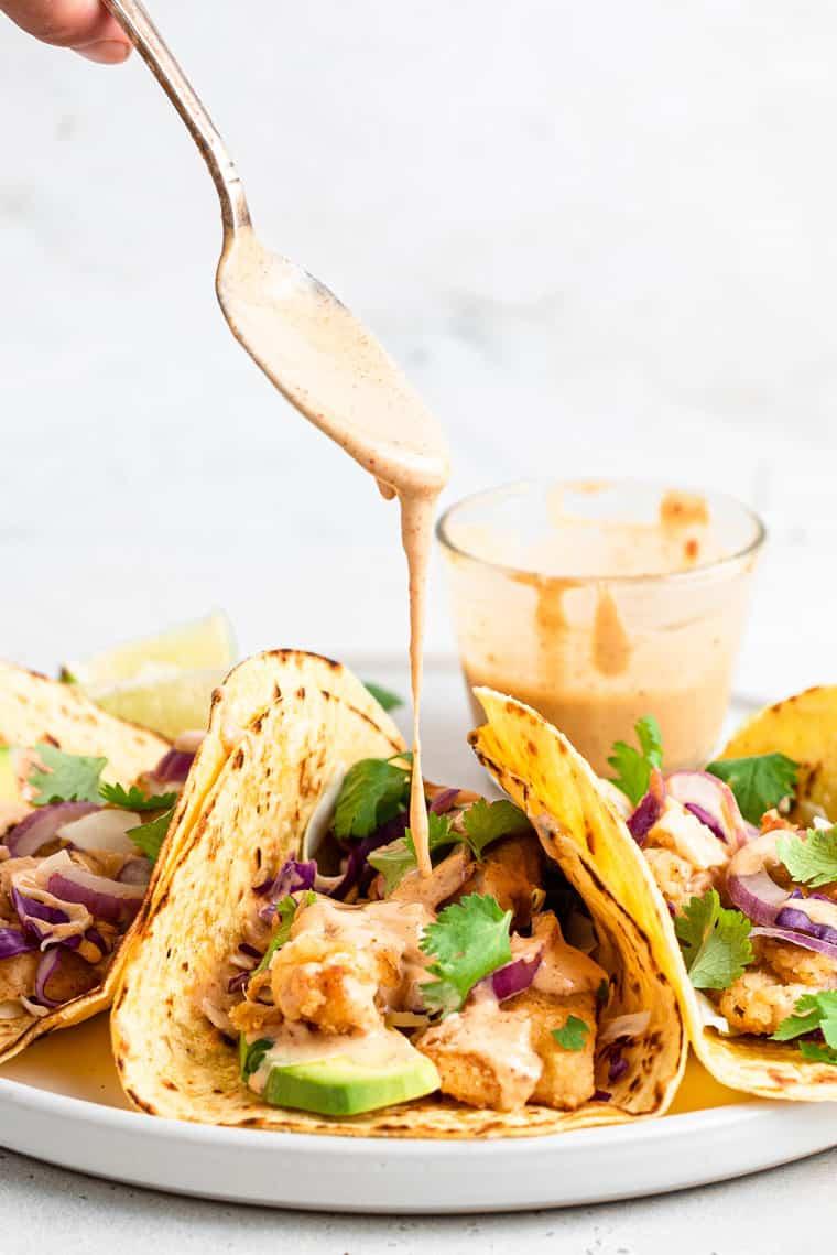 pouring tahini sauce over three crispy fish tacos