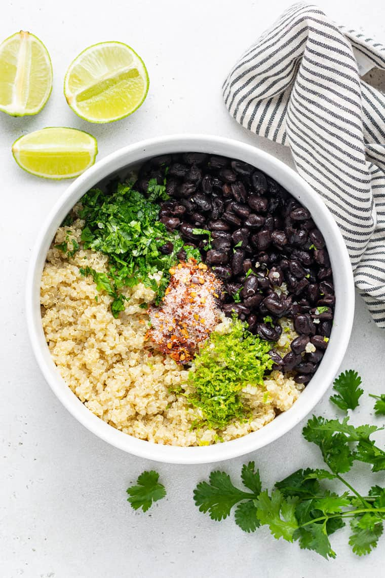 overhead of a white bowl with the ingredients for black bean, quinoa and cilantro salad