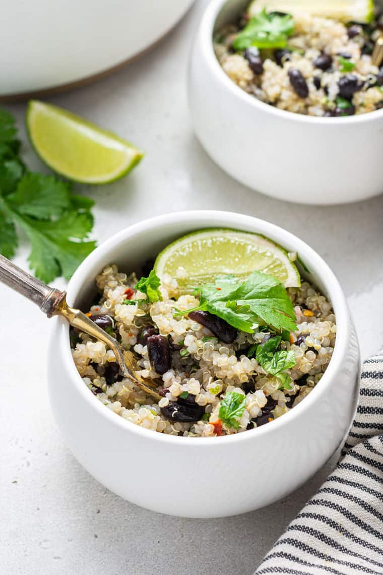 close up on a white bowl with cilantro lime quinoa and bean salad
