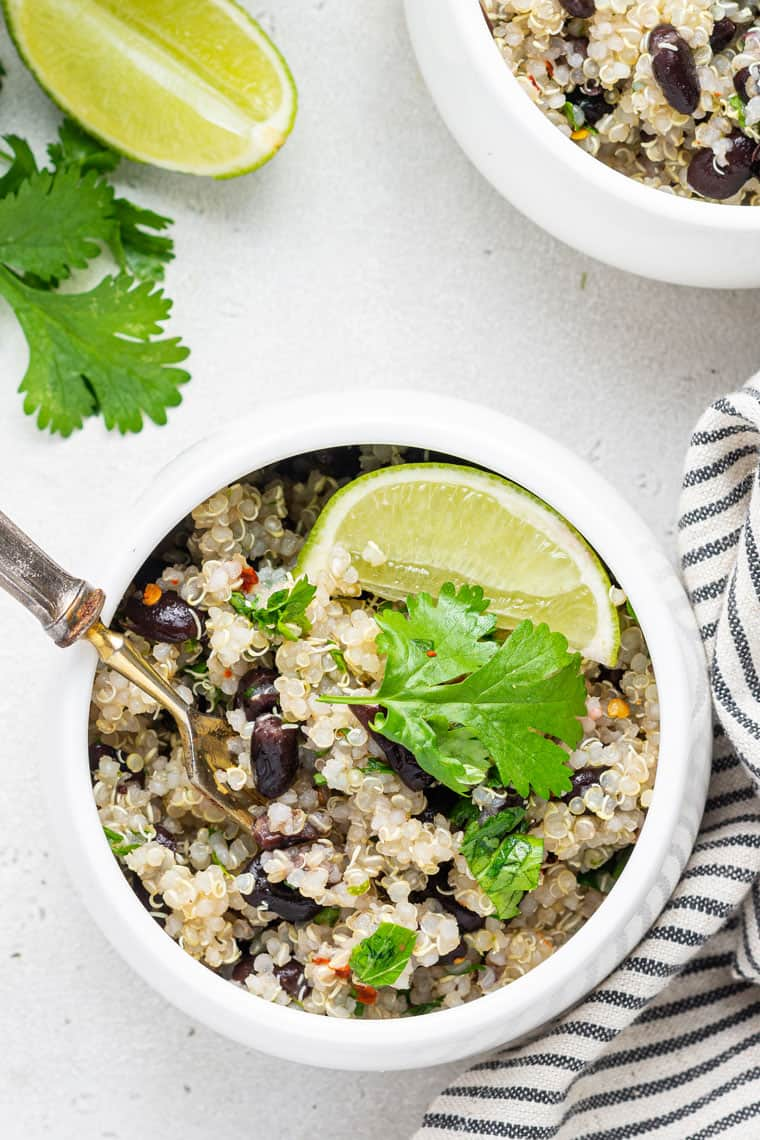 overhead of a white bowl with quinoa and bean salad and fresh limes