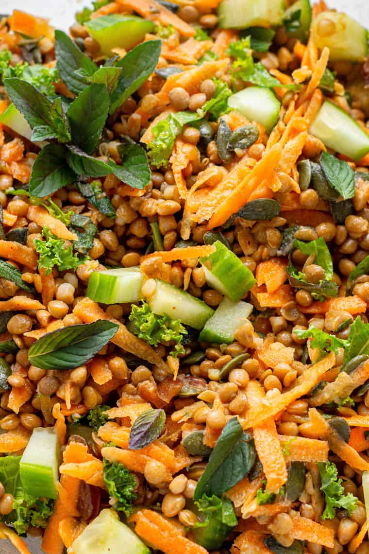 close up on curry lentil salad in clear bowl with cucumbers and carrots